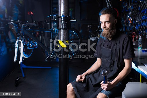 952953976istockphoto Portrait of small business owner of young man with beard. Guy bicycle mechanic workshop worker sitting with tool in his hand in a working black clothes in an apron in the background of a bicycle shop 1133364109