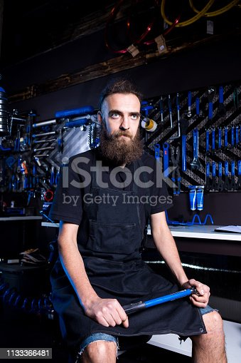 952953976istockphoto Portrait of small business owner of young man with beard. Guy bicycle mechanic workshop worker sitting with tool in his hand in a working black clothes in an apron in the background of a bicycle shop 1133366481