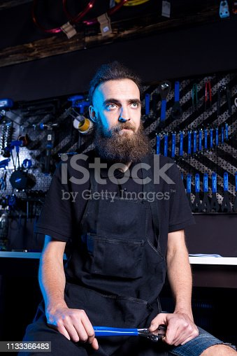 952953976istockphoto Portrait of small business owner of young man with beard. Guy bicycle mechanic workshop worker sitting with tool in his hand in a working black clothes in an apron in the background of a bicycle shop 1133366483