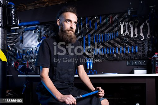 952953976istockphoto Portrait of small business owner of young man with beard. Guy bicycle mechanic workshop worker sitting with tool in his hand in a working black clothes in an apron in the background of a bicycle shop 1133366490