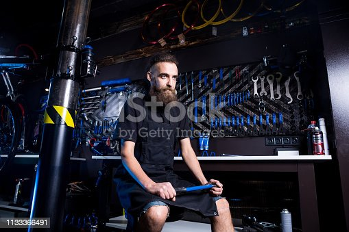 952953976istockphoto Portrait of small business owner of young man with beard. Guy bicycle mechanic workshop worker sitting with tool in his hand in a working black clothes in an apron in the background of a bicycle shop 1133366491