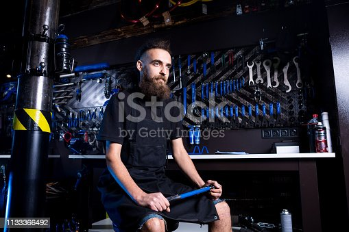 952953976istockphoto Portrait of small business owner of young man with beard. Guy bicycle mechanic workshop worker sitting with tool in his hand in a working black clothes in an apron in the background of a bicycle shop 1133366492