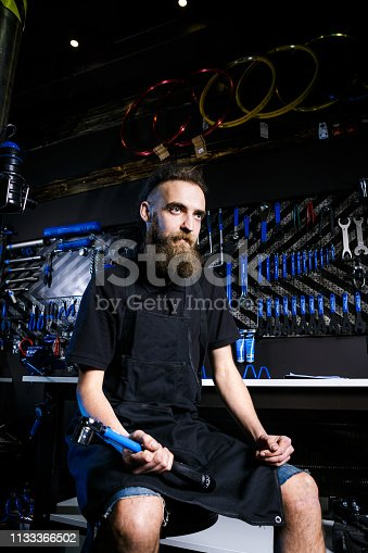 952953976istockphoto Portrait of small business owner of young man with beard. Guy bicycle mechanic workshop worker sitting with tool in his hand in a working black clothes in an apron in the background of a bicycle shop 1133366502