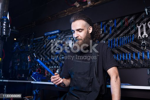 952953976istockphoto Portrait of small business owner of young man with beard. Guy bicycle mechanic workshop worker sitting with tool in his hand in a working black clothes in an apron in the background of a bicycle shop 1133366689