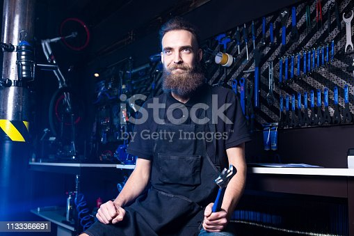 952953976istockphoto Portrait of small business owner of young man with beard. Guy bicycle mechanic workshop worker sitting with tool in his hand in a working black clothes in an apron in the background of a bicycle shop 1133366691
