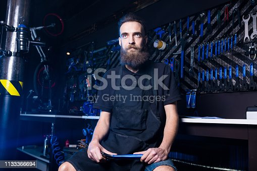 952953976istockphoto Portrait of small business owner of young man with beard. Guy bicycle mechanic workshop worker sitting with tool in his hand in a working black clothes in an apron in the background of a bicycle shop 1133366694