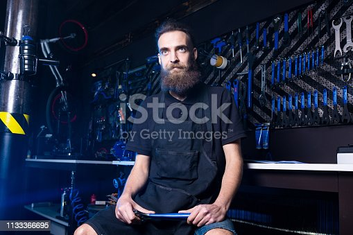 952953976istockphoto Portrait of small business owner of young man with beard. Guy bicycle mechanic workshop worker sitting with tool in his hand in a working black clothes in an apron in the background of a bicycle shop 1133366695