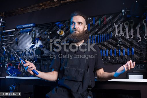 952953976istockphoto Portrait of small business owner of young man with beard. Guy bicycle mechanic workshop worker sitting with tool in his hand in a working black clothes in an apron in the background of a bicycle shop 1133366711