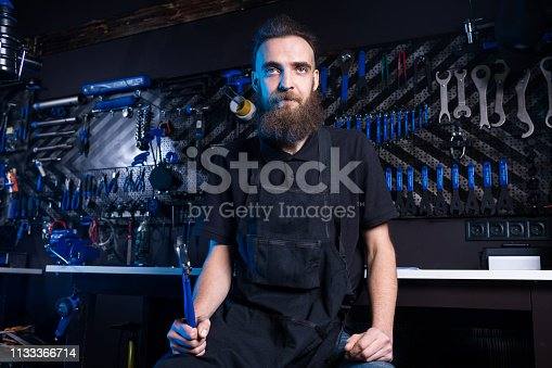 952953976istockphoto Portrait of small business owner of young man with beard. Guy bicycle mechanic workshop worker sitting with tool in his hand in a working black clothes in an apron in the background of a bicycle shop 1133366714