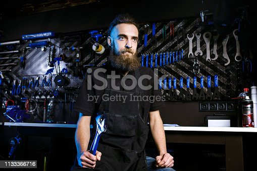 952953976istockphoto Portrait of small business owner of young man with beard. Guy bicycle mechanic workshop worker sitting with tool in his hand in a working black clothes in an apron in the background of a bicycle shop 1133366716