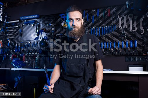 952953976istockphoto Portrait of small business owner of young man with beard. Guy bicycle mechanic workshop worker sitting with tool in his hand in a working black clothes in an apron in the background of a bicycle shop 1133366717