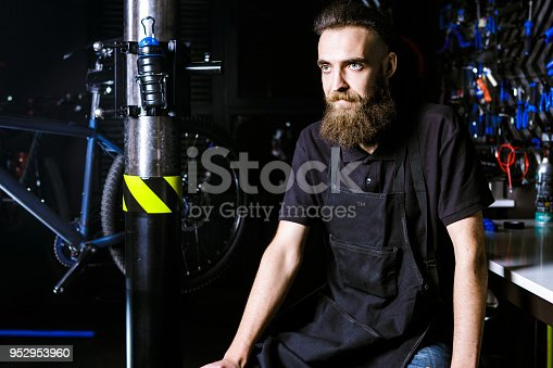 952953976istockphoto Portrait of small business owner of young man with beard. Guy bicycle mechanic workshop worker sitting with tool in his hand in a working black clothes in an apron in the background of a bicycle shop 952953960