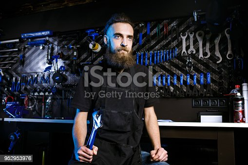 istock Portrait of small business owner of young man with beard. Guy bicycle mechanic workshop worker sitting with tool in his hand in a working black clothes in an apron in the background of a bicycle shop 952953976
