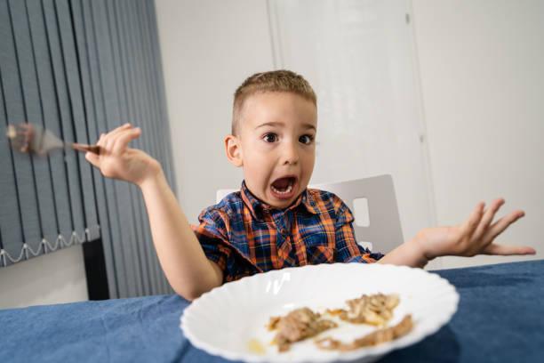 porträtt av små kaukasiska pojke lilla barn barn sitter vid bordet äta lunch eller middag hålla gaffel gör ansikten gest frontvy hemma ser med öppna munnen undrar - bordsskick bildbanksfoton och bilder