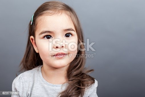 Small girl looking at camera on the grey background