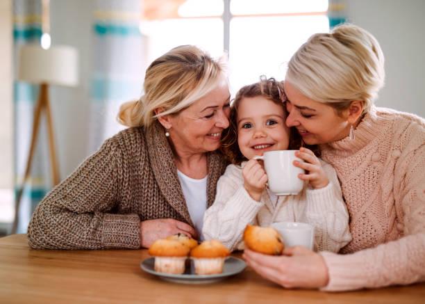 un portrait de petite fille avec la mère et la grand-mère à la table à la maison. - tasse flat photos et images de collection
