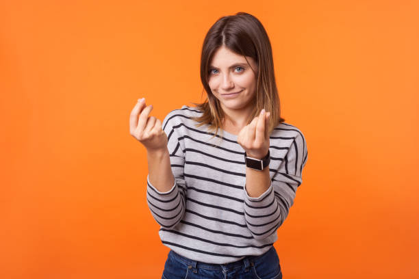 Portrait of smart beautiful woman with brown hair in long sleeve striped shirt. indoor studio shot isolated on orange background stock photo