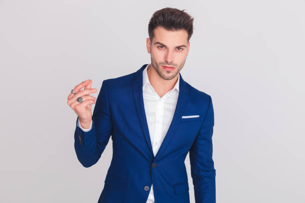portrait of smart casual man in blue suit snapping fingers portrait of smart casual man in blue suit snapping his fingers while standing on light grey background snapping stock pictures, royalty-free photos & images