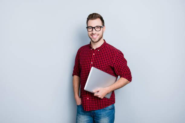 市松模様のカジュアル シャツ、ジーンズ、保持閉じ手で、灰色の背景に分離されたネットブック赤い服を着てスマート巧妙な修飾された有望な it スペシャ リストのソフトウェア開発者の肖� - オタク ストックフォトと画像