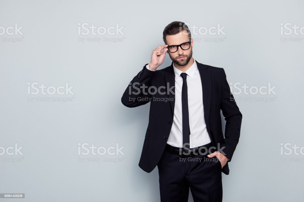 Portrait of smart intelligent handsome virile experienced qualified rich luxurious stylish glamorous clever nerd investor banker broker correcting fixing glasses accessory isolated on gray background stock photo