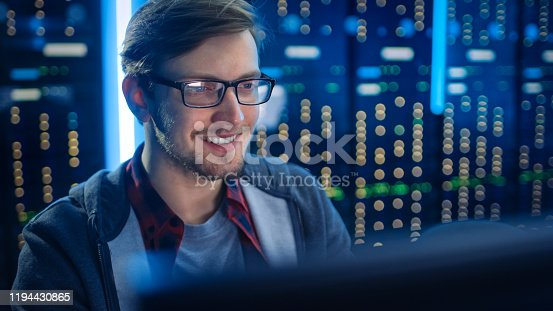 1154261912 istock photo Portrait of Smart SmilingFocused Young Man Wearing Glasses Working on Desktop Computer. In Background Technical Department Office with Functional Data Server Racks. 1194430865