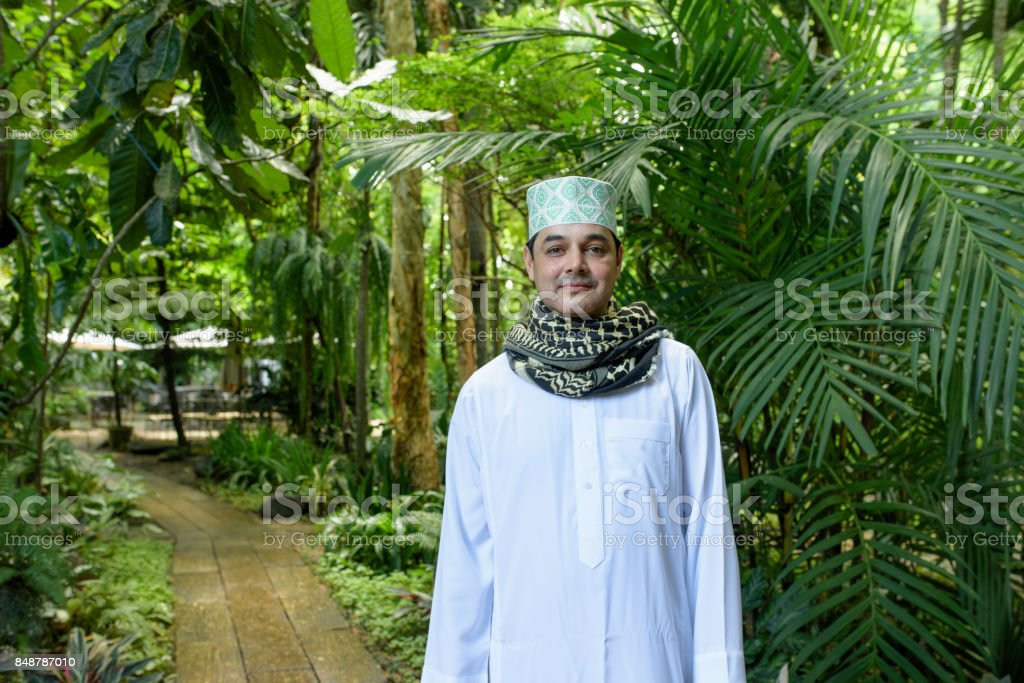 Portrait of smile handsome Arab muslim man in meshlah - white dress and prayer cap on head with red yashmagh on neck in half length in outdoor garden stock photo