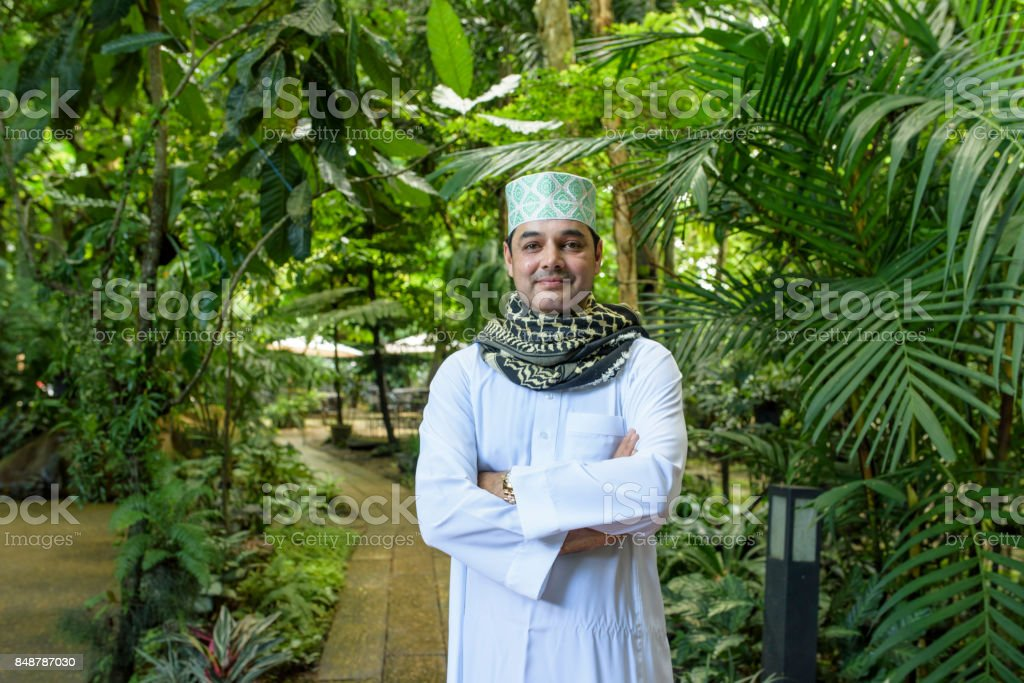 Portrait of smile handsome Arab muslim man in meshlah - white dress and prayer cap on head with red yashmagh on neck in half length and cross his arm standing in outdoor garden . stock photo
