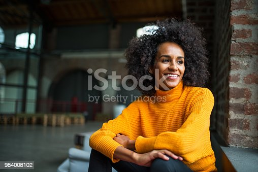 Portrait of smiling African American woman looking trow the window