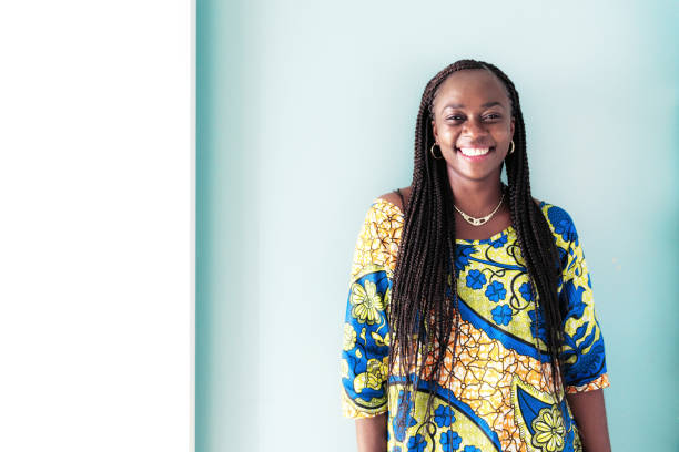 portrait of smiling african woman in front of blue wall stock photo