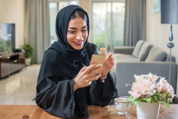 Porträt des lächelnden arabischen Mädchens, das Handy zu Hause benutzt – Foto