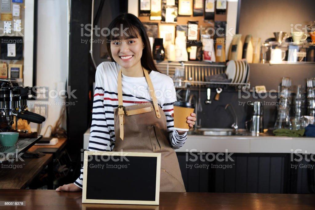 Porträt des Lächelns asiatischen Barista Tasse Kaffee mit leere Tafel Menü am Schalter im Coffee-Shop. Cafe Restaurant Service, Essen und trinken Industrie Konzept. – Foto