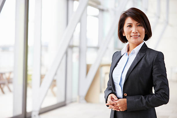 portrait of smiling asian businesswoman, standing - woman suit stock photos and pictures