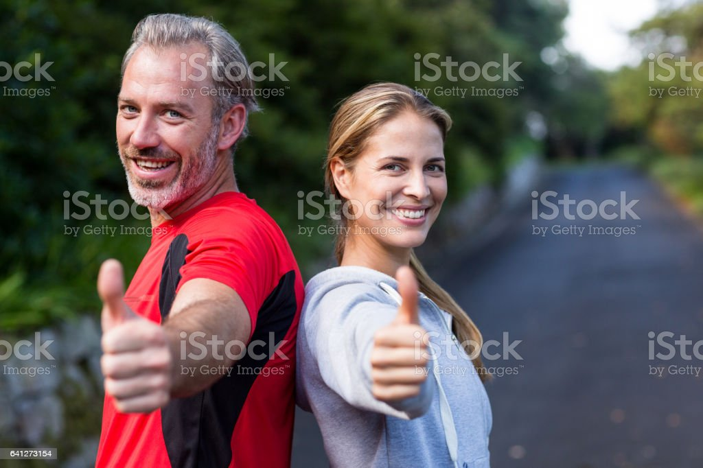 Portrait of smiling athletic couple showing thumbs up stock photo