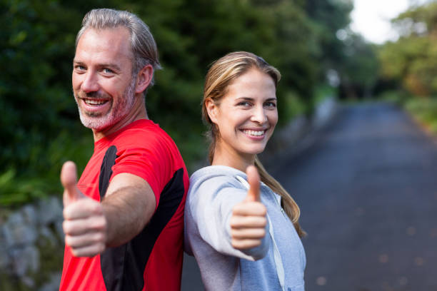 portrait of smiling athletic couple showing thumbs up - mid adult couple stock pictures, royalty-free photos & images