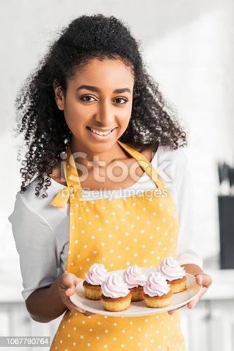 istock portrait of smiling attractive african american girl in apron holding homemade cupcakes and looking at camera in kitchen 1067790764