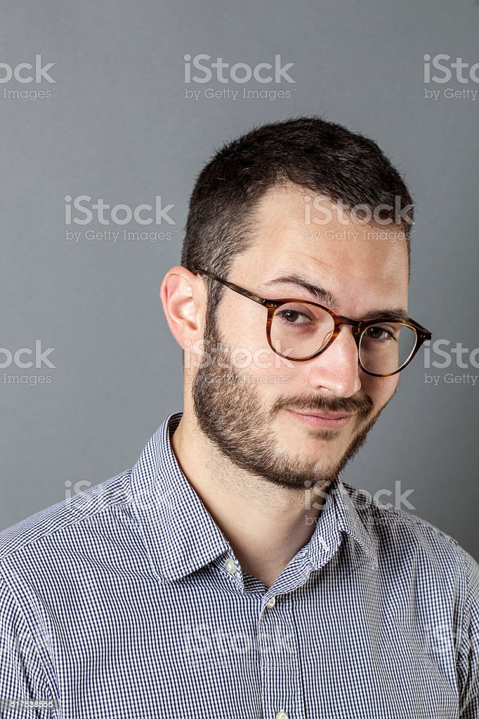 portrait of smiling bearded young entrepreneur with eyeglasses looking satisfied stock photo