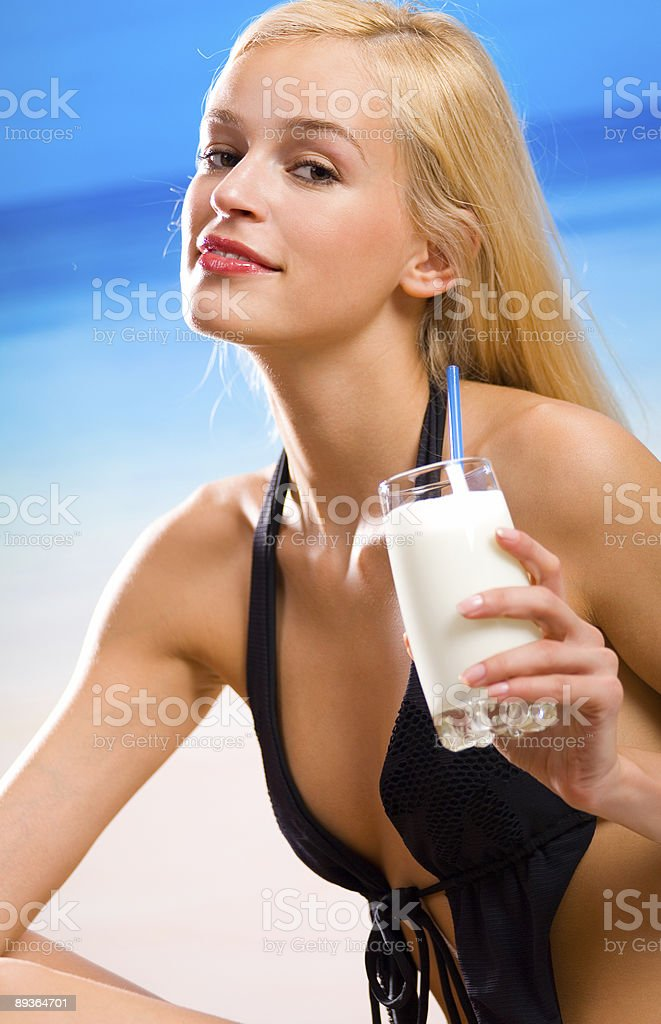 Portrait of smiling beautiful woman with milkshake on sea beach royalty-free stock photo