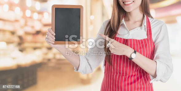 istock Portrait of Smiling beautiful young Asian woman wear red apron and holding a small square black board with copy space for your text or advertising on blurred shop and supermarket background. 874222168