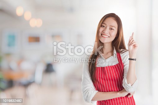 istock Portrait of Smiling beautiful young Asian woman wear red apron and hand pointing with copy space for your text or advertising on blurred cafe background. 1019832482
