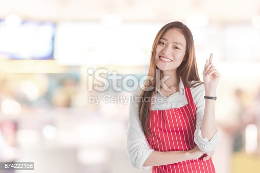 istock Portrait of Smiling beautiful young Asian woman wear red apron and hand pointing with copy space for your text or advertising isolated on blurred shop and supermarket background. 874222158