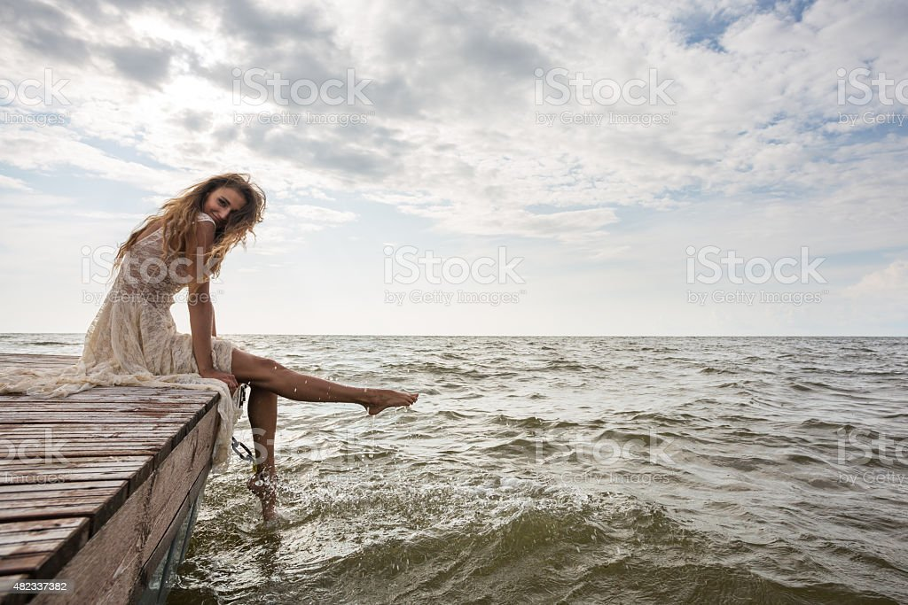 Portrait of smiling beautiful young woman sitting on a pier stock photo