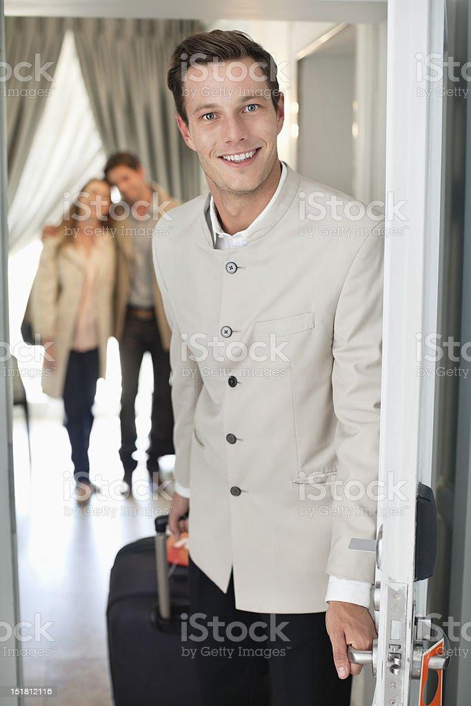 Portrait of smiling bellman in hotel doorway stock photo