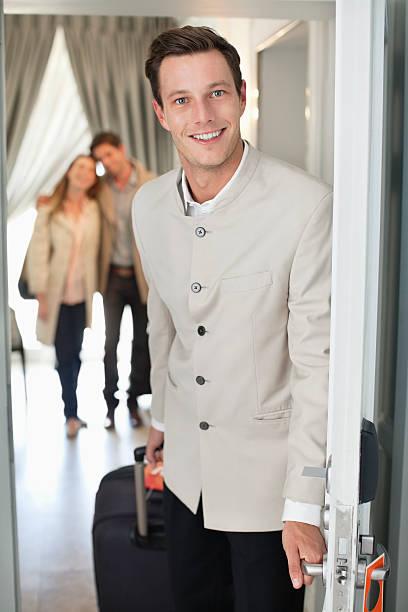 Retrato de la sonriente botones de entrada del hotel - foto de stock
