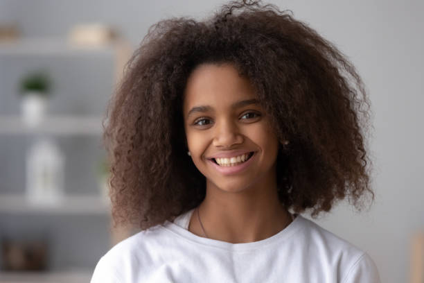 Portrait of smiling black teenage girl posing at home Portrait of happy African American teen girl looking at camera at home, headshot of smiling black teenager posing indoors, beautiful mixed race teenage female laughing making picture young girls on webcam stock pictures, royalty-free photos & images