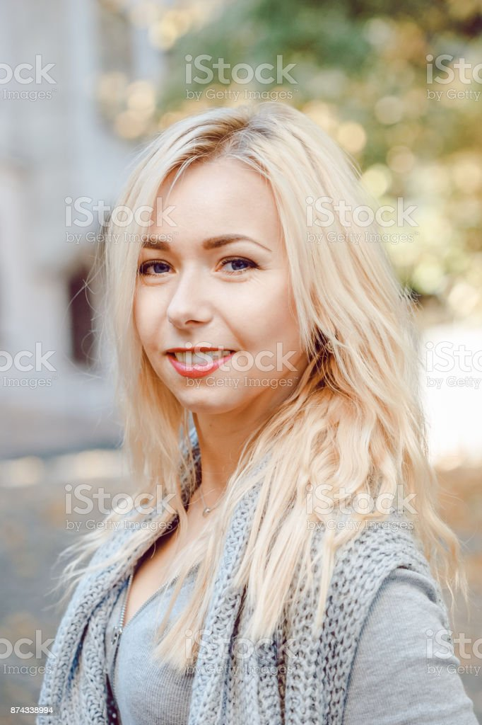 Portrait of smiling blonde woman standing outdoors stock photo