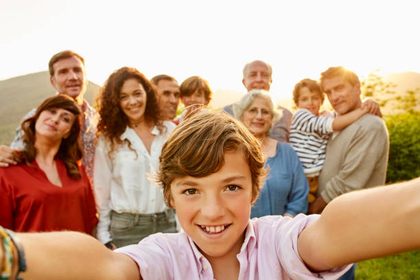 portrait of smiling boy against family in yard - multi generation family stock photos and pictures
