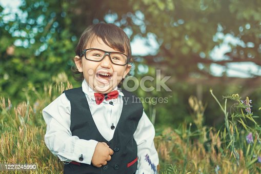 Smiling little boy in suit and glasses with long hair.Portrait of smiling boy against trees in forest
