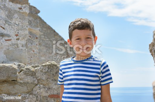 Beautiful little child near sea. Looking in camera