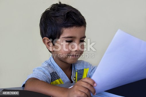 istock Portrait of smiling boy looking at paper holding 483826900
