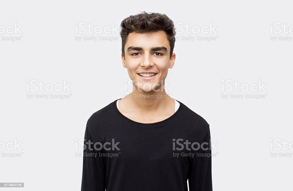 Portrait of smiling boy over gray background stock photo